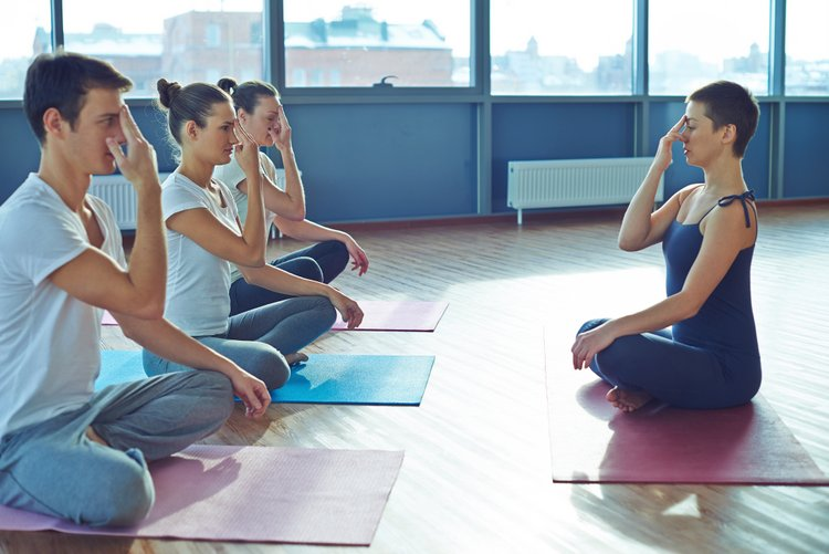 Spiritual exercise coach teaching young people how to do yoga exercises